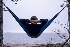 O turista é sonhos e pensativo sérios quando descansar em uma rede após o seguimento imagem de stock