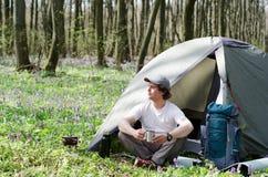 O turista bebe o chá em um acampamento da barraca Foto de Stock Royalty Free