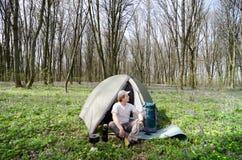 O turista bebe o chá em um acampamento da barraca Imagem de Stock Royalty Free