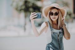 O turista brincalhão atrativo novo está fazendo o selfie no telefone fora, vestindo o chapéu, óculos de sol imagens de stock royalty free