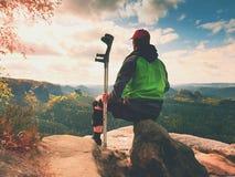 O turista cansado do homem senta-se com o joelho de dano no imobilizador ou balança-se, guarda-se o polo da medicina Abra a paisa fotografia de stock royalty free