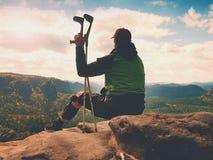 O turista cansado do homem senta-se com o joelho de dano no imobilizador ou balança-se, guarda-se o polo da medicina Abra a paisa fotografia de stock
