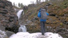 O turista com uma trouxa escala acima em uma rocha em uma cachoeira da montanha Alcançou a extremidade da rota Aventuras ativas video estoque