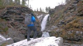 O turista com uma trouxa escala acima em uma rocha em uma cachoeira da montanha Alcançou a extremidade da rota Aventuras ativas filme
