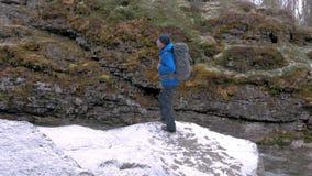 O turista com uma trouxa escala uma rocha por um rio da montanha Aventuras e curso ativos vídeos de arquivo