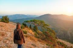 O turista com uma trouxa está no alvorecer no conceito do terreno montanhoso do curso fotos de stock royalty free