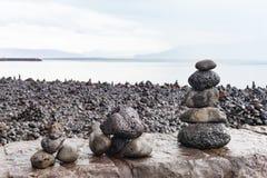 O turista construiu pilhas de rochas em Reykjavik na parede de mar Fotografia de Stock