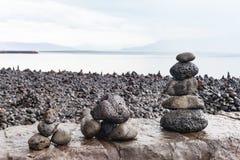 O turista construiu pilhas de rochas em Reykjavik na parede de mar Fotografia de Stock Royalty Free