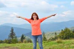 O turista da menina em brilhante fecha estar na montanha, levantando as mãos e o sorriso feliz montanhas, nuvens no fundo imagens de stock