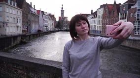O turista da menina faz o selfi em um smartphone em um fundo da cidade de Bruges Bélgica vídeos de arquivo