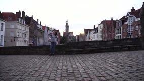 O turista da menina faz o selfi em um smartphone em um fundo da cidade de Bruges Bélgica video estoque