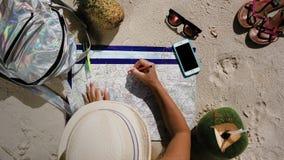O turista da menina na praia verifica a rota vídeos de arquivo