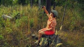 O turista da menina nos óculos de sol e em um boné de beisebol na floresta senta-se em uma árvore caída e toma-se imagens no tele vídeos de arquivo