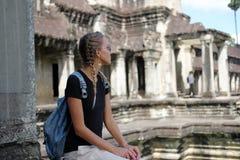 O turista da mulher com óculos de sol e as tranças aproximam o templo antigo Angkor Wat, Cambodia imagem de stock