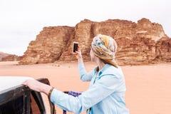 O turista da mulher dispara no vídeo ou na foto no telefone celular do deserto jordano foto de stock