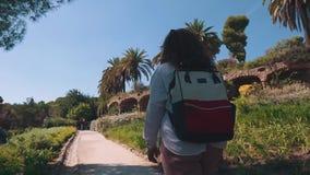 O turista da mulher está andando sobre o trajeto na área bonita do parc com palmas tropicais filme