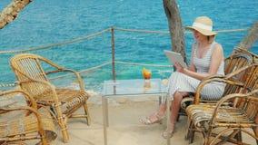 O turista da mulher fala com a tabuleta, sempre-na conexão Videochat do ponto cênico que negligencia o mar filme