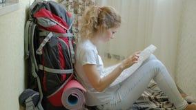 O turista da mulher recolhe coisas em uma trouxa na cozinha da casa e prepara-se para os olhares da viagem no papel video estoque