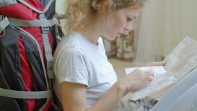 O turista da mulher recolhe coisas em uma trouxa na cozinha da casa e prepara-se para os olhares da viagem no papel vídeos de arquivo