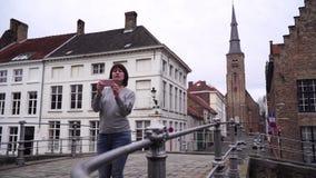 O turista da mulher toma o pictureson no smartphone em Bruges Bélgica filme