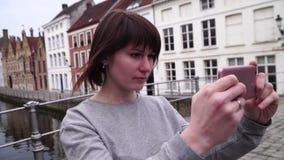 O turista da mulher toma o pictureson no smartphone em Bruges Bélgica Movimento lento filme