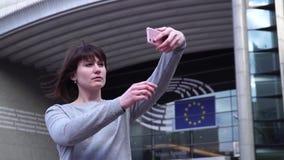 O turista da mulher toma o pictureson no smartphone perto do Parlamento Europeu em Bruxelas bélgica filme