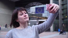 O turista da mulher toma o pictureson no smartphone perto do Parlamento Europeu em Bruxelas bélgica video estoque
