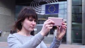 O turista da mulher toma o pictureson no smartphone perto do Parlamento Europeu em Bruxelas bélgica vídeos de arquivo