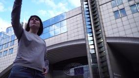 O turista da senhora faz o selfie no smartphone perto do Parlamento Europeu em Bruxelas bélgica vídeos de arquivo