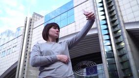 O turista da senhora faz o selfie no smartphone perto do Parlamento Europeu em Bruxelas bélgica Movimento lento vídeos de arquivo
