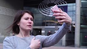 O turista da senhora faz o selfie no smartphone perto do Parlamento Europeu em Bruxelas bélgica Movimento lento filme