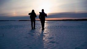O turista de dois homens com trouxas está nas montanhas no inverno contra coberto de neve Dois amigos viajam junto dentro filme