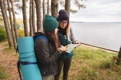 O turista de dois jovens determina o mapa e o compasso de rota fotografia de stock royalty free
