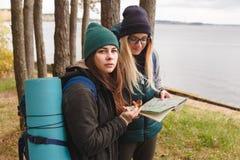 O turista de dois jovens determina o mapa e o compasso de rota imagem de stock royalty free