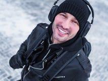 O turista de Smling nos fones de ouvido anda na rua Tempo de inverno Fotografia de Stock
