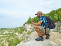 O turista do homem está usando um smartphone ao sentar-se na borda da Imagem de Stock