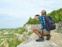 O turista do homem está usando um smartphone ao sentar-se na borda da Fotografia de Stock Royalty Free