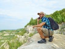 O turista do homem está usando um smartphone ao sentar-se na borda da Foto de Stock Royalty Free