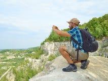O turista do homem está usando um smartphone ao sentar-se na borda do CLI Fotos de Stock