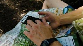 O turista do homem senta nas verificações da floresta a rota em um mapa e em um telefone de papel usando GPS em um smartphone Toc filme