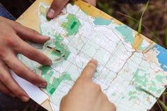 O turista dois determina o mapa e o compasso de rota Fotos de Stock