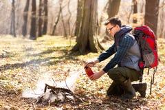 O turista extingue o fogo do extintor, ap?s um resto na natureza imagem de stock