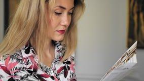 O turista fêmea caucasiano bonito está considerando uma brochura não reconhecida no museu Movimento lento filme