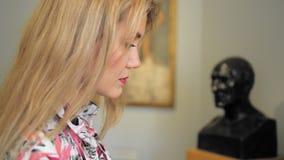 O turista fêmea caucasiano bonito está considerando uma exibição não reconhecida no museu Movimento lento video estoque