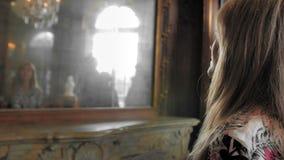 O turista fêmea caucasiano bonito olha si mesma em um espelho medieval do vintage luxuoso Movimento lento filme