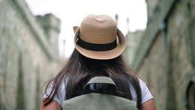 O turista fêmea do caminhante do baixo ângulo que admira o steadicam antigo da opinião traseira da construção estabelece o tiro vídeos de arquivo