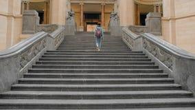 O turista f?mea novo escala uma grande escadaria de m?rmore O conceito da prosperidade do neg?cio, eleva??o financeira Movimento