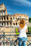 O turista fêmea novo olha o Colosseum em Roma Fotos de Stock Royalty Free
