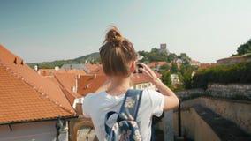 O turista fêmea novo toma a foto pelo telefone de telhados de telha vermelha em República Checa filme