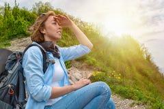 O turista fêmea sentou-se para baixo para descansar sobre a montanha e os olhares na distância Fim acima Fundos: luz do sol fotos de stock